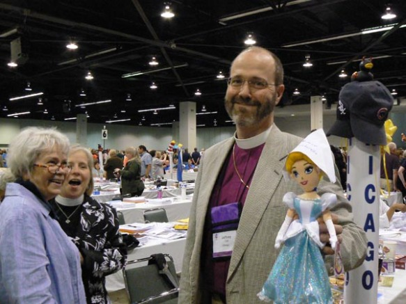 Bishop Jeffrey Lee makes friends with the Bishop Cinderella doll at the Chicago deputation table. Looking on are Deputy Vicki Garvey and Alternate Shawn Schreiner. Photo by Scott Hayashi.