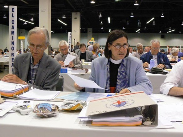 Deputies Newland Smith and the Rev. Bonnie Perry file committee reports and resolutions during the July 9 legislative session.